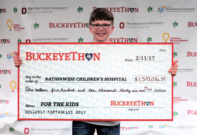 BuckeyeThon Kid Josh holds the 2017 presentation check for Nationwide Children's Hospital